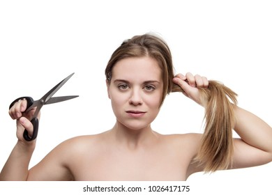 young woman with long hair cutting it of with a pair of scissors having a bad hair day