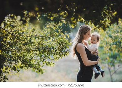 Young woman with long hair looks happy holding little girl posing under the tree in a sunny day
