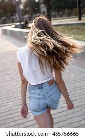 Young woman with long hair on the street at sunset. Back view