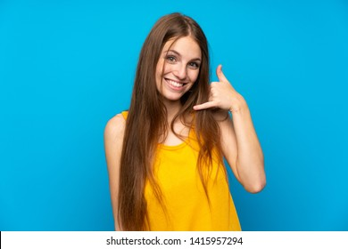 Young woman with long hair over isolated blue wall making phone gesture. Call me back sign