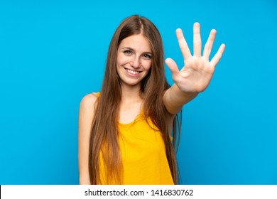 Young woman with long hair over isolated blue wall counting five with fingers