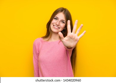 Young woman with long hair over isolated yellow wall counting five with fingers