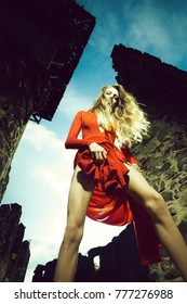 Young woman with long hair in sexy red dress outdoor on green grass near ruined stony building sunny day with blue sky