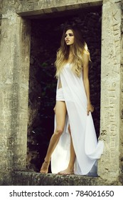 Young woman with long hair in sexy white dress and jeans outdoor in door arch of ruined stony building