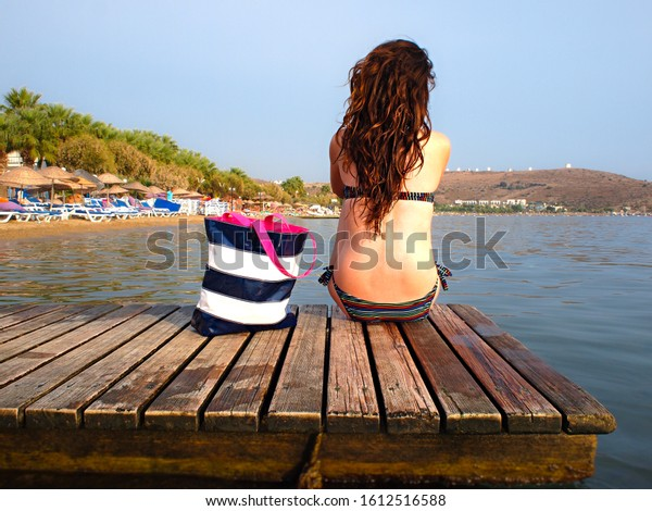 Young woman with long hair sits on a wooden deck watching the calm sea water in Bodrum Turkey
