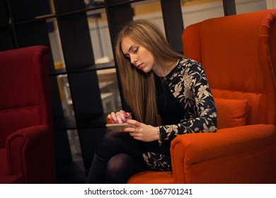 Young woman with long hair is sitting in a red armchair and is looking at the phone