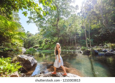 Young woman with long hair standing near silent river with clean water among green tropical jungle on the way to Aling-Aling waterfall on Bali island, Indonesia