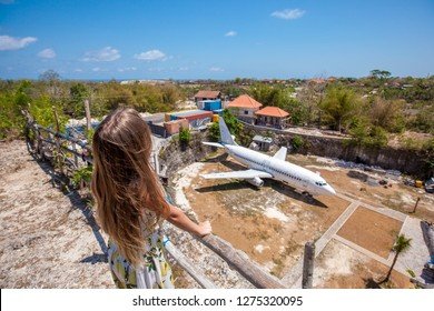 Young woman with long hair standing back with the background of big white abandoned passenger plane among rocks and green trees on the Bali island, Indonesia