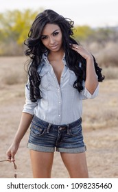 Young woman with long hair wearing denim top and shorts in desert location.