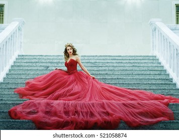 Young woman in a long red dress and gold crown sitting on the stairs