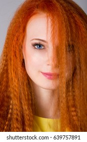 Young woman with long red hair in studio
