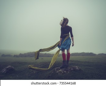 A young woman with a long scarf blowing in the wind is standing on the moor in the fog