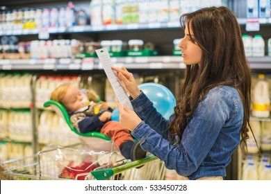 Young woman with a long shopping list in. Little son sleeping in shop