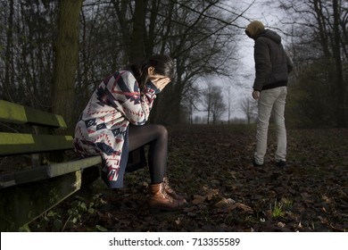 A young woman with a long sweater sitting on a bench in dark forest.She covers her eyes while crying.A man is looking back.A concept about being attacked,hurt,harrased or raped.Hard flash light image.