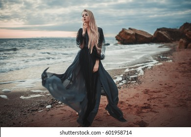 Young woman in long transparent black dress among beach and sea. Wind blows hem of her dress.
