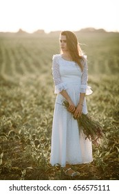 Young woman in long white lace dress on cornfield. She stands with bouquet of wild flowers in her hands.