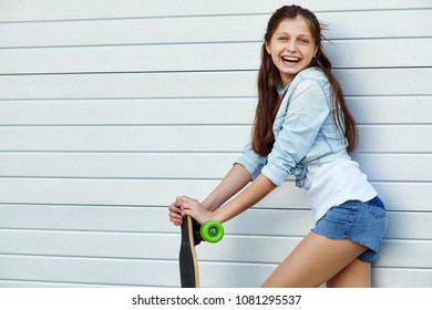 young woman with a longboard. trendy casual hipster teenage girl with a skateboard