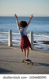 Young woman longboarding by the ocean on sunny day, riding skateboarding on sidewalk