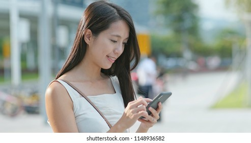 Young Woman look at the smart phone in city