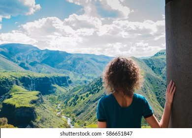 Young woman looking at amazing view. Female traveler contemplate impressive mountains landscape. Girl explore world. Summer vacation. Majestic nature. Travel lifestyle. Ecotourism concept. Copy space
