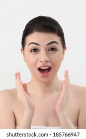 Young woman looking away with mouth open in surprise,