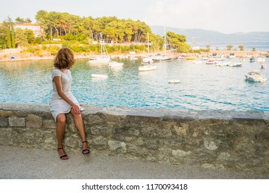 Young woman is looking at the bay full off ships in Krk town on island Krk in Croatia.  Female admiring the view from above full of vessels in adriatic town. Travel and holiday concept.