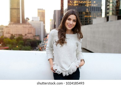 Young woman looking beautiful, sitting on a bridge across the boulevard in urban scenery, downtown, at sunset, smiling at camera.