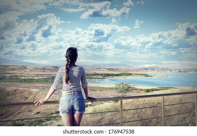 Young woman looking at a beautiful view of the lake and mountains