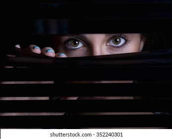 Young woman looking behind a blind