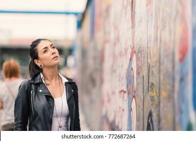 Young woman looking at Berlin Wall.