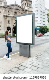 Young woman looking at a billboard in the city