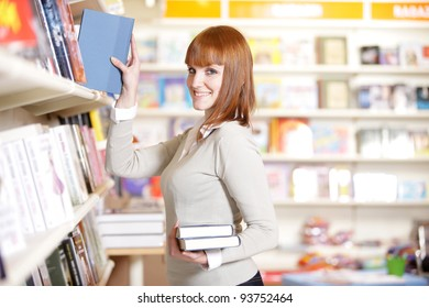 young woman looking for a book in a bookstore