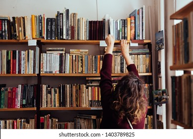 Young woman looking for a book in a library. May 2019 - Braila, Romania.