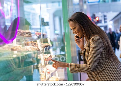 Young woman looking in a cake shop window