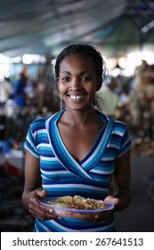 Young woman looking at camera, eating while working at a street market in Nairobi (Kenya)