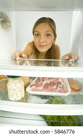 Young woman looking at the camera from fridge. On one shelf lying for example meat and jar of marinated garlic. Front view