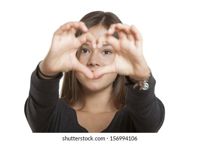 Young woman looking at camera making one heart with her fingers