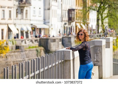 Young woman is looking at the camera in old part of Ljubljana, Slovenia