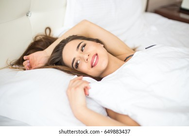 Young woman looking at camera and smiling while lying on the bed