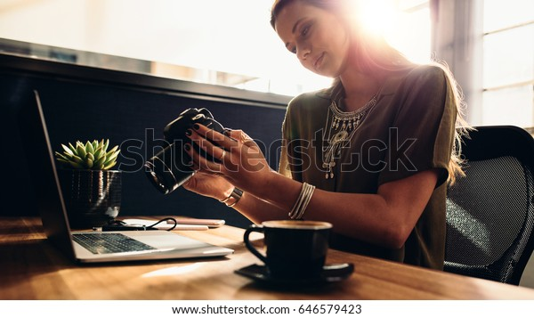 Young woman looking at camera while working on laptop. Photographer with her camera and laptop on her desk.