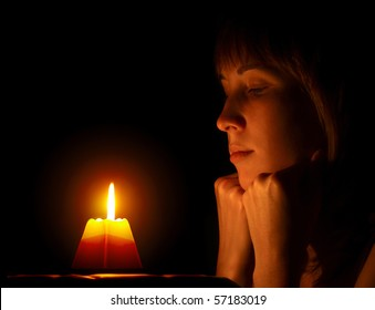 Young woman looking to a candle