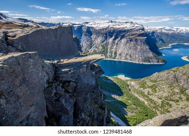 Young woman looking carefully over the edge of Trolltunga in Norway