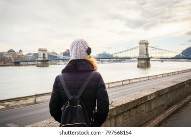 Young woman is looking at the Chain bridge from Danube riverbank by the road in Budapest, Hungary.