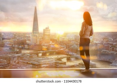 Young woman looking at the City of London, financial district. Early morning. Sun rise. Future, planning and business progress concept.