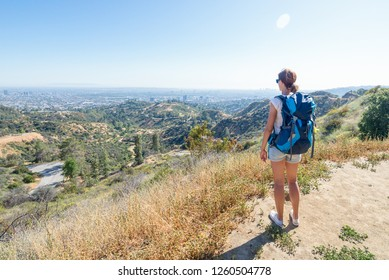 Young woman is looking at the city of Los Angeles, California, USA from Griffith Park. Travel and adventure concept.