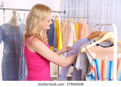Young woman looking clothes on rack at showroom