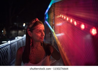young woman looking at colorful light on building