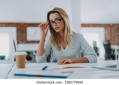 Young woman looking curious while sitting at her workplace in the office and touching the glasses