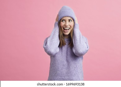 Young woman looking cute with sweater and matching hat on colorful background