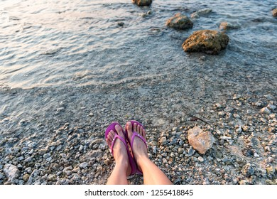 Young woman looking down pov point of view perspective on feet flip-flops sandals sitting on rocky beach in Islamorada, Florida Keys, legs